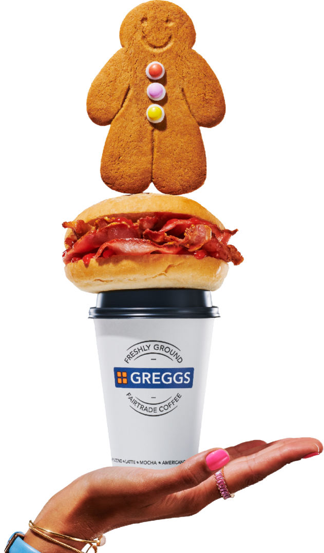 Hand holding Greggs hot drink, bacon roll and gingerbread person